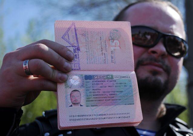 Biker russo fa vedere il suo passaporto con visto Schengen annullato