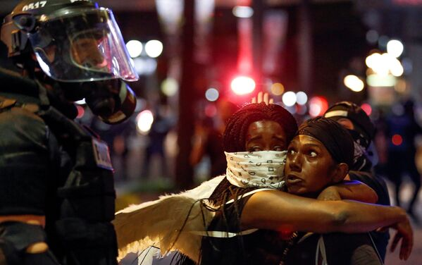 Due donne si abbracciano di fronte a un poliziotto durante le proteste a Charlotte, USA. - Sputnik Italia