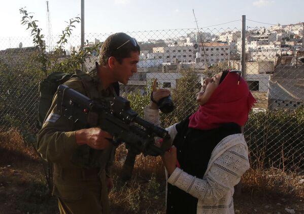 Un soldato israeliano litiga con una donna palestinese. - Sputnik Italia