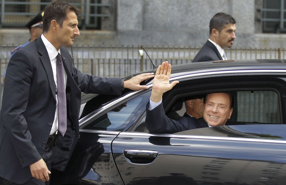 L-ex premier guarda giornalisti dalla sua macchina dopo aver lasciato il Tribunale di Milano.