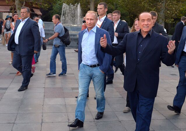 Russian President Vladimir Putin (3rd R) and Italy's former prime minister Silvio Berlusconi (R) walk along the Yalta embankment in Crimea on September 11, 2015