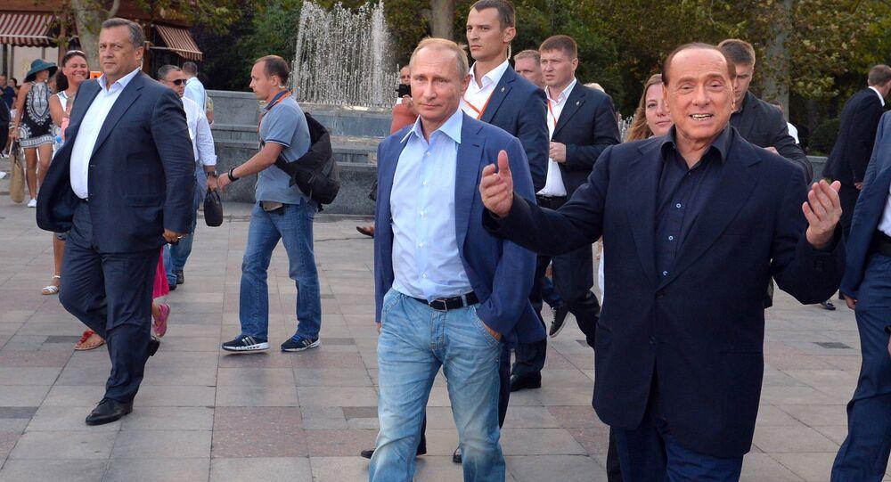 Russian President Vladimir Putin (3rd R) and Italy's former prime minister Silvio Berlusconi (R) walk along the Yalta embankment in Crimea on September 11, 2015