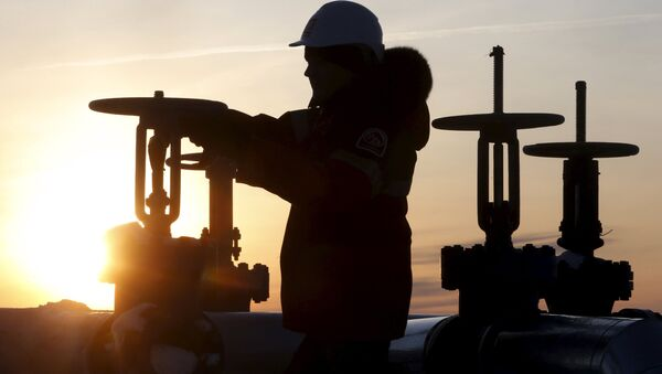 A worker checks the valve of an oil pipe at the Lukoil company owned Imilorskoye oil field outside the West Siberian city of Kogalym, Russia, January 25, 2016 - Sputnik Italia