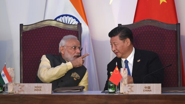 India Prime Minister Narendra Modi (L) gestures while talking with China's President Xi Jingping during the BRICS leaders' meeting with the BRICS Business Council at the Taj Exotica hotel in Goa on October 16, 2016 - Sputnik Italia