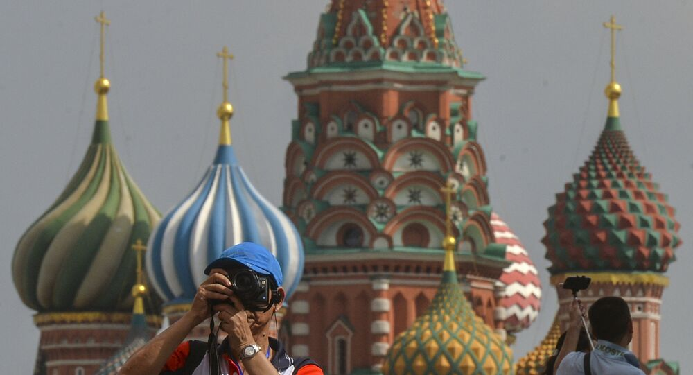 A tourist takes pictures on Red Square, Moscow.