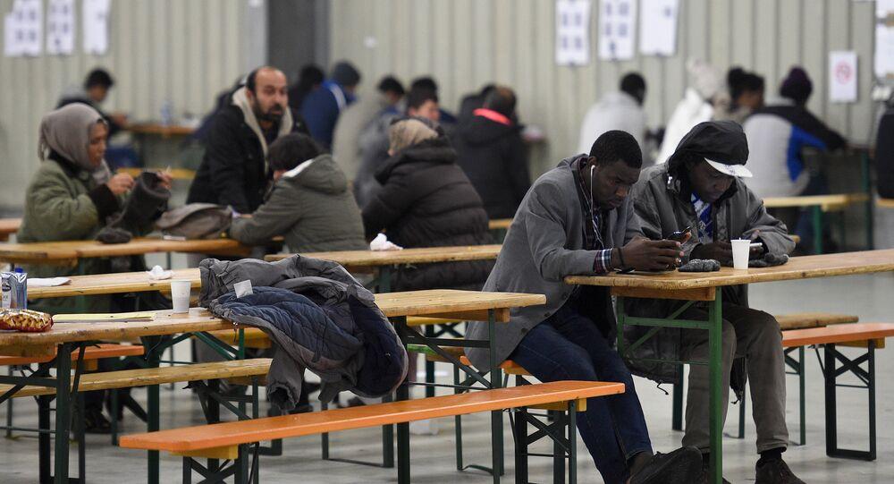 Immigrati usano i loro telefoni in una mensa nella bassa sassonia
