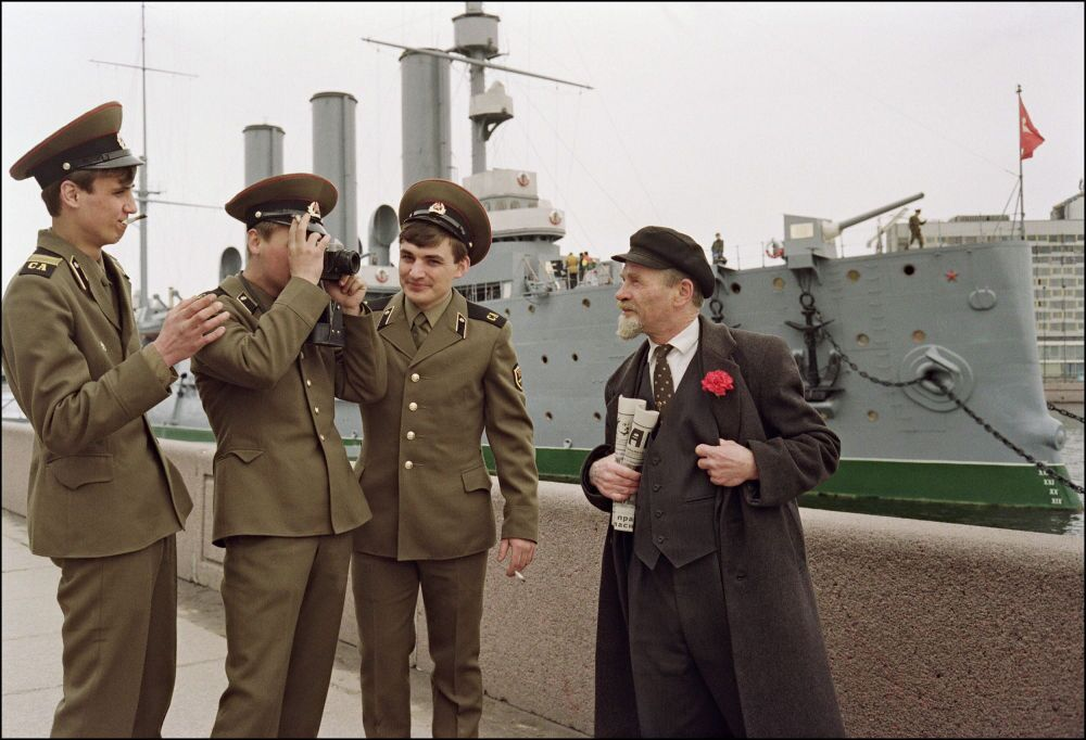 Un sosia di Vladimir Lenin in posa per una foto davanti all'incrociatore Aurora