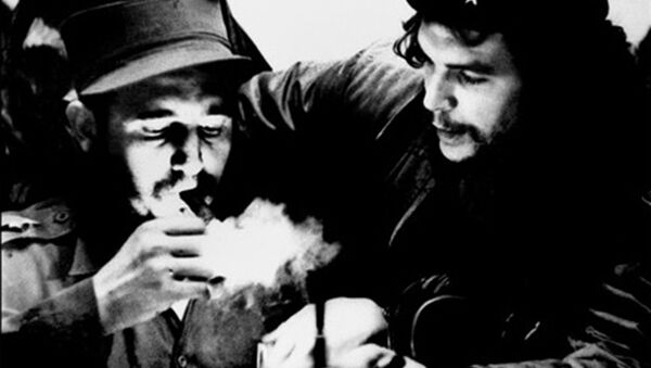 (FILES) This file photo taken in the 1960s shows then Cuban Prime Minister Fidel Castro (L) lighting a cigar while listens Argentine Ernesto Che Guevara - Sputnik Italia