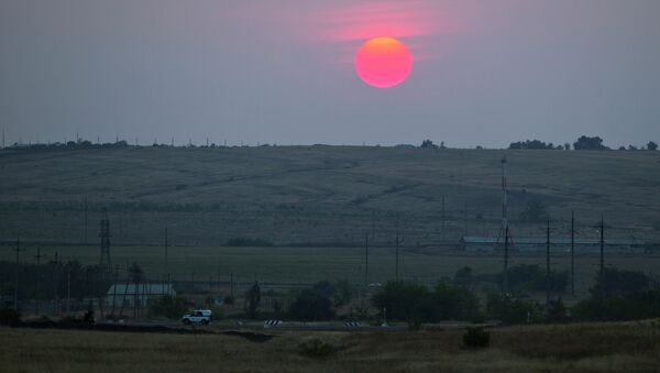 A police car moves in an emptied field where trucks of the aid convoy were parked about 28 kilometers (17 miles) from the Ukrainian border, near Kamensk-Shakhtinsky, Rostov-on-Don region, Russia, during sunset at Friday, Aug. 22, 2014 - Sputnik Italia