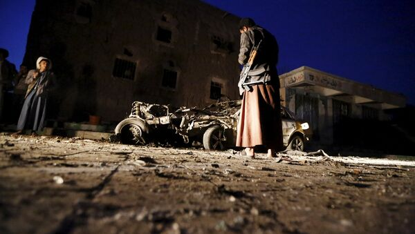 An armed man looks at the wreckage of a car at the site of a car bomb attack in Yemen's catpital Sanaa June 17, 2015 - Sputnik Italia