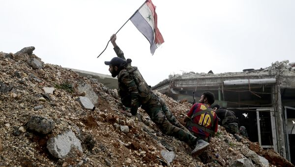 Syrian army soldier places a Syrian national flag during a battle with rebel fighters at the Ramouseh front line, east of Aleppo, Syria - Sputnik Italia