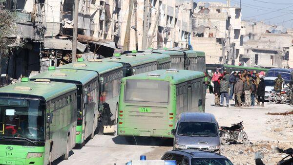 People get on buses to be evacuated from al-Sukkari rebel-held sector of eastern Aleppo, Syria December 15, 2016. - Sputnik Italia