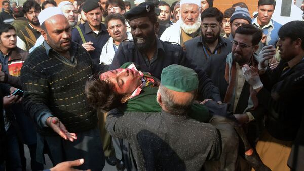 Hospital security guards carry a students injured in the shootout at a school under attacked by Taliban gunmen in Peshawar, Pakistan,Tuesday, Dec. 16, 2014 - Sputnik Italia