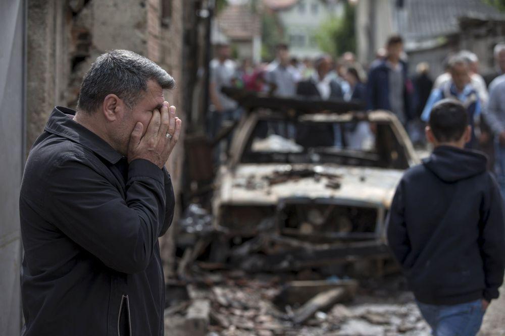 Un uomo piange davanti alla sua auto distrutta a Kumanovo.