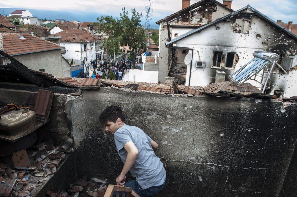 Un bambino tra le macerie di una casa.