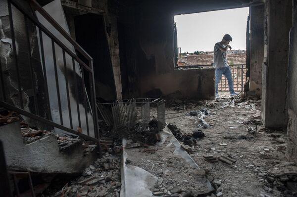 Un giovane sulla soglia della sua casa distrutta durante gli scontri a Kumanovo. - Sputnik Italia