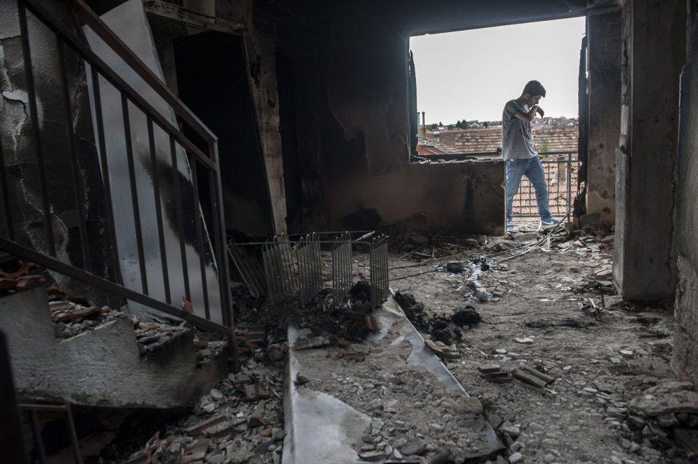 Un giovane sulla soglia della sua casa distrutta durante gli scontri a Kumanovo.