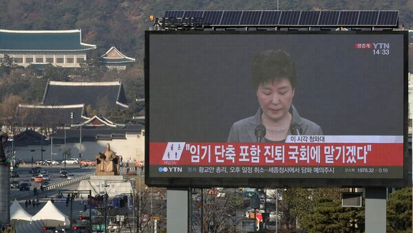 A large electronic board broadcasts a news report on South Korean President Park Geun-hye releasing a statement to the public as the Presidential Blue House (top L) is seen in the background, in central Seoul, South Korea, November 29, 2016. - Sputnik Italia