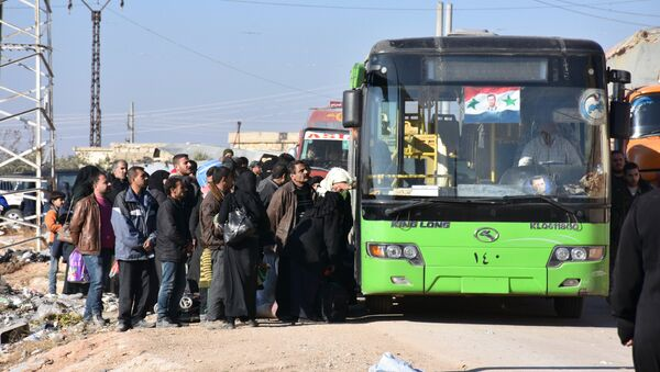 Syrian residents fleeing the violence, queue as they board a bus at a checkpoint, manned by pro-government forces, in the village of Aziza on the southwestern outskirts of the northern Syrian city of Aleppo on December 9, 2016 - Sputnik Italia