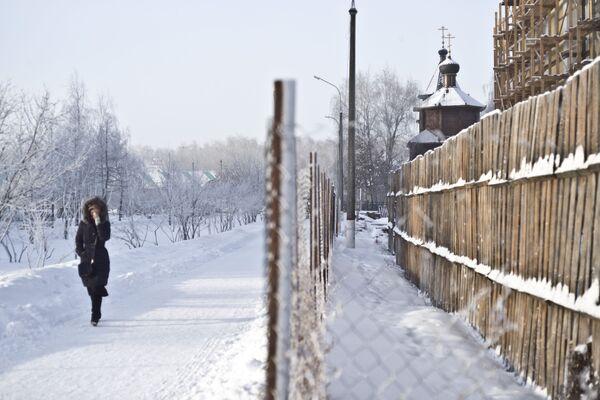 Una donna vicino a una chiesa che viene costruita nel quartiere di Zhulebino a Mosca. - Sputnik Italia