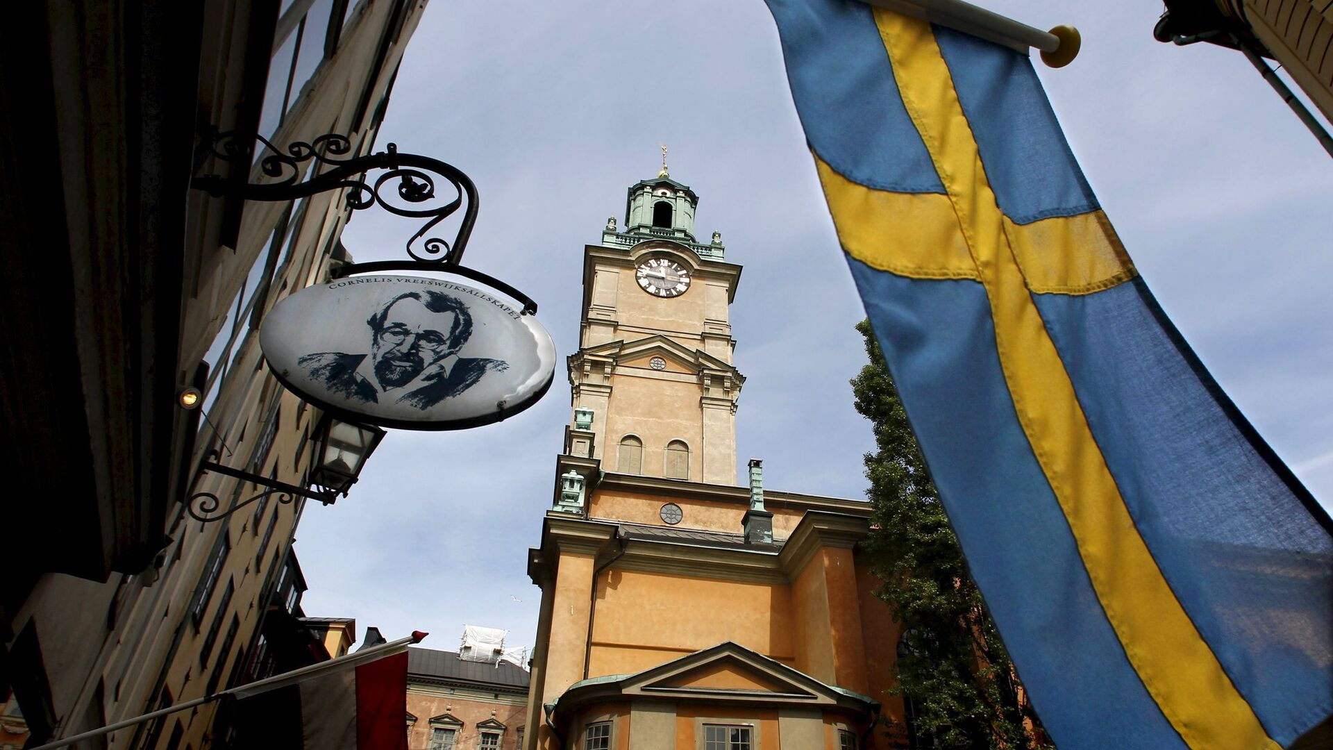Sweden's flag is seen near the Stockholm Cathedral in Gamla Stan or the Old Town district of Stockholm, Sweden - Sputnik Italia, 1920, 10.09.2021