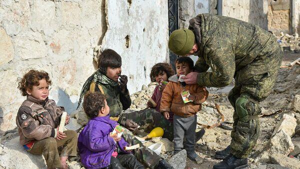 Soldato russo con dei bambini per le strade di Aleppo - Sputnik Italia