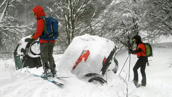 Members of Lazio's Alpine and Speleological Rescue Team are seen next to cars covered in snow in front of the Hotel Rigopiano in Farindola, central Italy, hit by an avalanche, in this January 19, 2017 handout picture provided by Lazio's Alpine and Speleological Rescue Team - Sputnik Italia