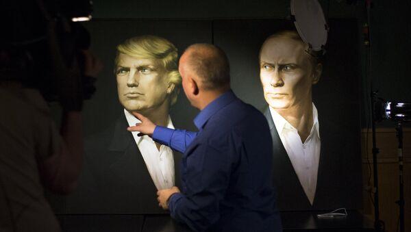 A journalist points at a portrait of U.S. President-elect Donald Trump, with a portrait of Russian President Vladimir Putin - Sputnik Italia