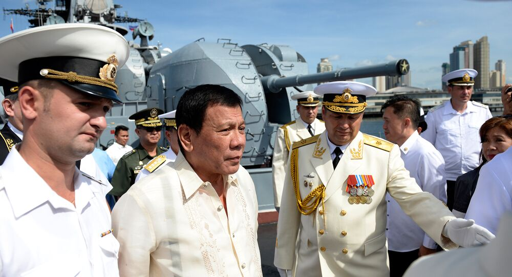 Russia's Rear Admiral Eduard Mikhailov (R) leads the way as he guides Philippines' President Rodrigo Duterte (2nd L) onboard the Russian anti-submarine navy ship Admiral Tributs in Manila on January 6, 2017
