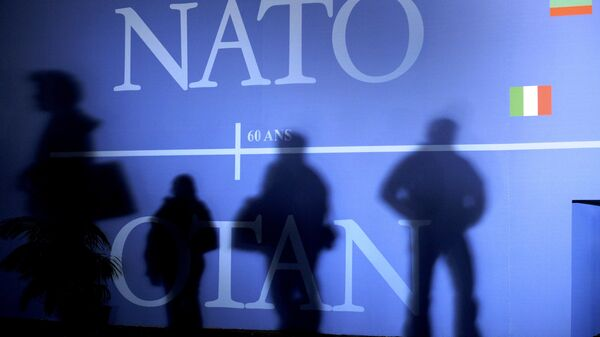 This April 2, 2009 file photo shows shadows cast on a wall decorated with the NATO logo and flags of NATO countries in Strasbourg, eastern France, before the start of the NATO summit which marked the organisation's 60th anniversary. - Sputnik Italia
