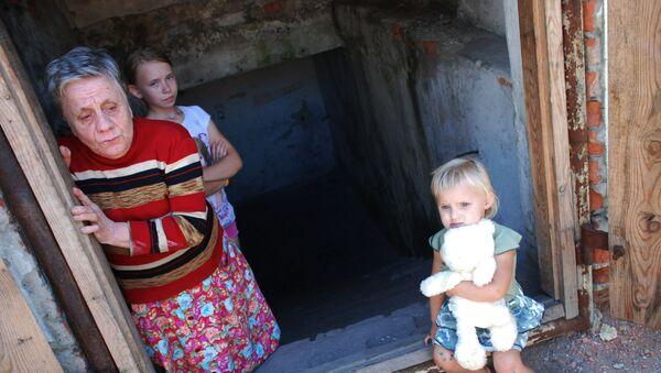 Bambini e una donna che vivono in un rifugio antiaereo in uno dei quartieri nella periferia di Donetsk. - Sputnik Italia