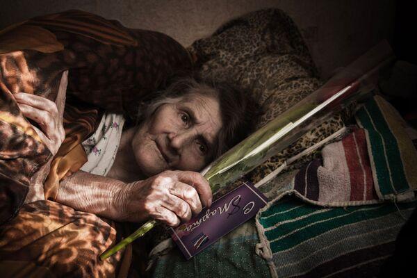 Una donna anziana celebra l'8 marzo, Giornata internazionale di donne, in un ospedale di Debaltsevo. - Sputnik Italia