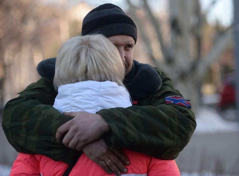 Una donna saluta un miliziano di DNR prima di partire in autobus con gli altri rifugiati da Donetsk in Russia.