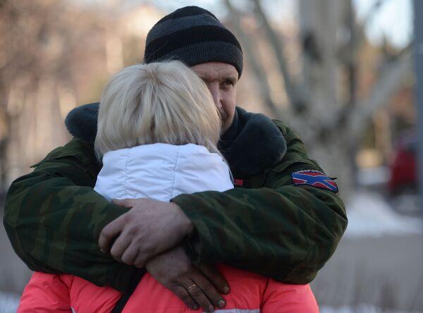 Una donna saluta un miliziano di DNR prima di partire in autobus con gli altri rifugiati da Donetsk in Russia. - Sputnik Italia