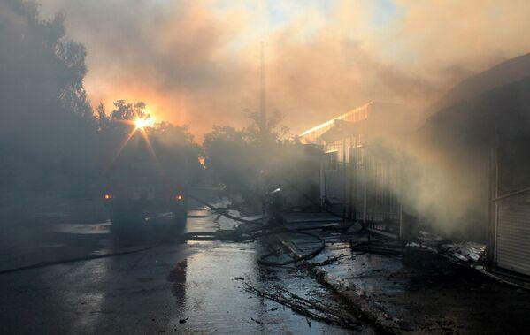Vigili di fuoco estinguono un incendio al mercato Oktyabrsky causato da un proettile durante un bombordamento nella città di Donetsk. - Sputnik Italia