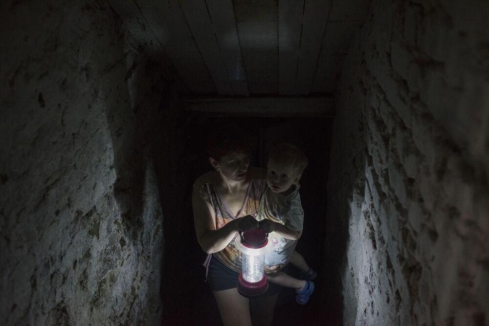 Una donna si nasconde con suo figlio nella cantina della sua casa a Gorlovka.