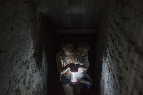 Una donna si nasconde con suo figlio nella cantina della sua casa a Gorlovka. - Sputnik Italia
