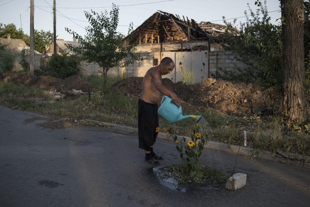 Un uomo annaffia i fiori in una delle vie della località di Veseloje nella regione di Donetsk.