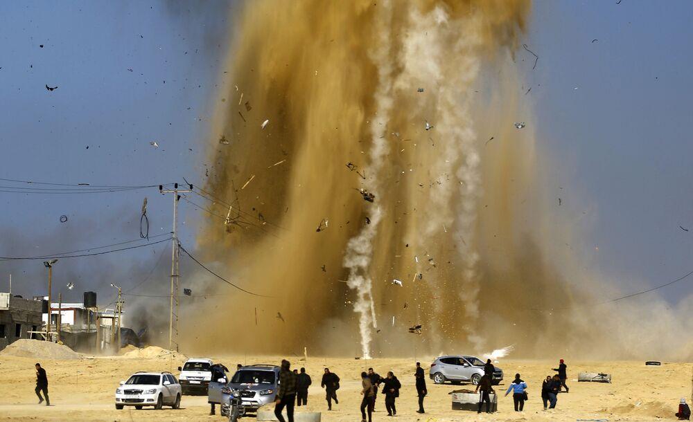 Palestinesi stanno correndo verso un rifugio dal luogo dell'esplosione dopo i bombradamenti aerei nel Gaza.
