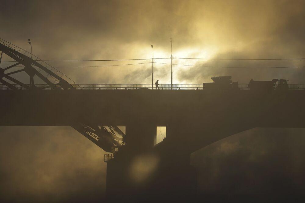Un uomo passa sul ponte sopra la Moscova.