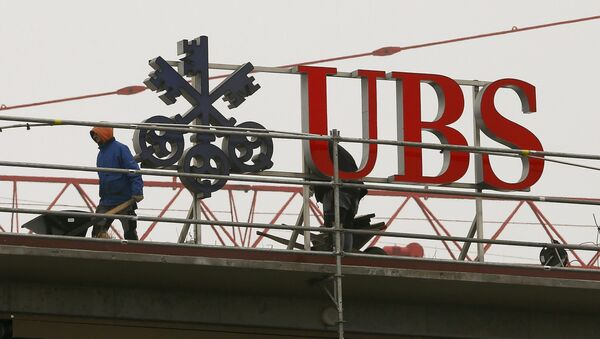 Workers are seen beside a logo of Swiss bank UBS in Zurich - Sputnik Italia