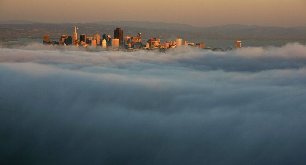 The skyline of San Francisco appears above the evening fog as the suns sets on the Marin Headlands in Sausalito, California