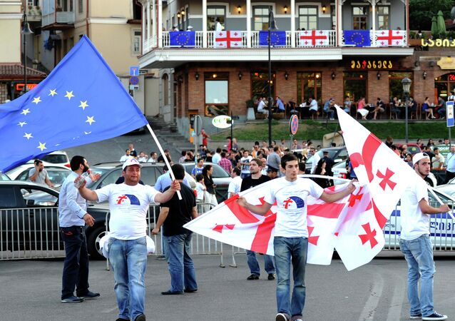 People wave the flags of Georgia (R) and the European Union (L) during celebrations for the signing of an association agreement with the EU in Tbilisi on June 27, 2014