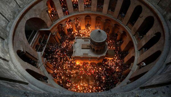 Верующие со свечами во время сошествия благодатного огня в Храм Гроба Господня в Иерусалиме - Sputnik Italia