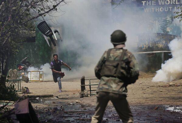 Uno studente di Kashmir getta una sedia contro un poliziotto indiano durante gli scontri a Srinagar. - Sputnik Italia