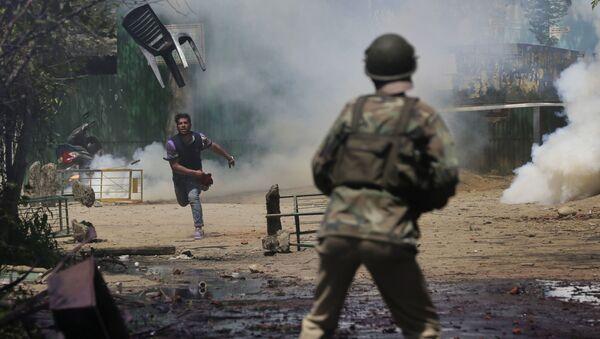 Кашмирский студент бросает стул в индийского полицейского во время столкновений в Сринагаре - Sputnik Italia