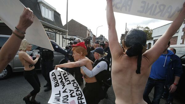 Femen activists, ones wearing the mask of Marine Le Pen, left, and U.S President Donald Trump, center, are detained as they demonstrate in Henin Beaumont, northern France, where far-right leader and presidential candidate Le Pen will vote, during the first round of the French presidential election - Sputnik Italia
