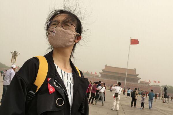 Una ragazza porta una maschera per proteggersi dallo smog. Piazza Tiananmen, Pekino, Cina. - Sputnik Italia