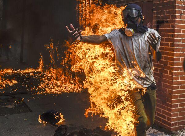 Un manifestante ha preso fuoco durante le manifestazioni contro il presidente della Venezuela Nicolas Maduro a Caracas. - Sputnik Italia