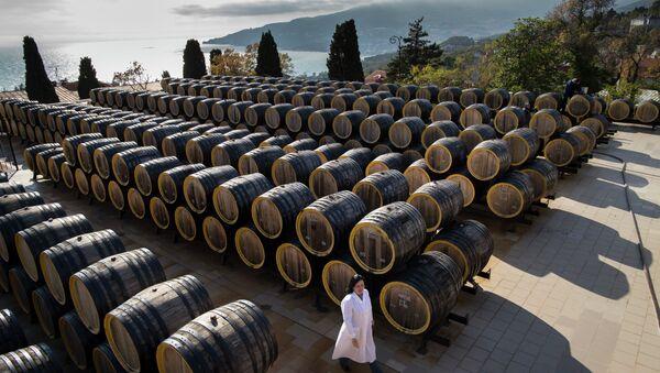 In this photo taken on Tuesday, Oct. 28, 2014, Rameta Kushkhova walks by barrels of wine in the state-owned Massandra winery in Yalta, Crimea - Sputnik Italia